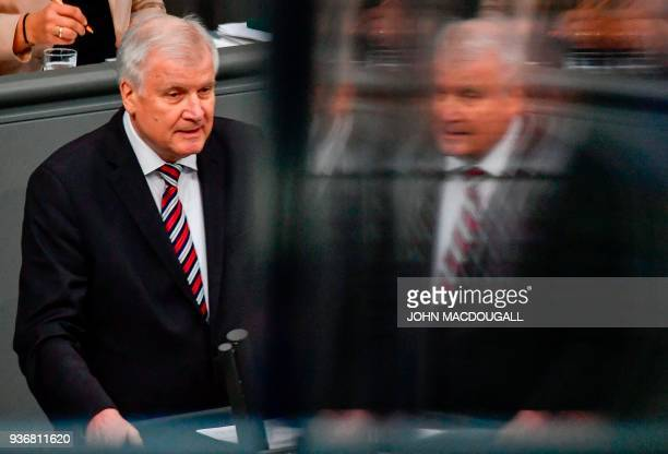 German Interior Minister Horst Seehofer addresses the lower house of parliament the Bundestag during a session on MArch 23 2018 in Berlin / AFP PHOTO...