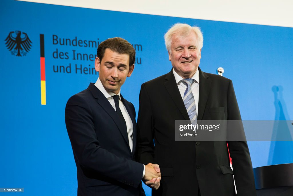German Interior Minister Horst Seehofer (R) and Austrian Chancellor Sebastian Kurz (L) shake hands at the end of a press conference at the Interior Ministry in Berlin, Germany on June 13, 2018.