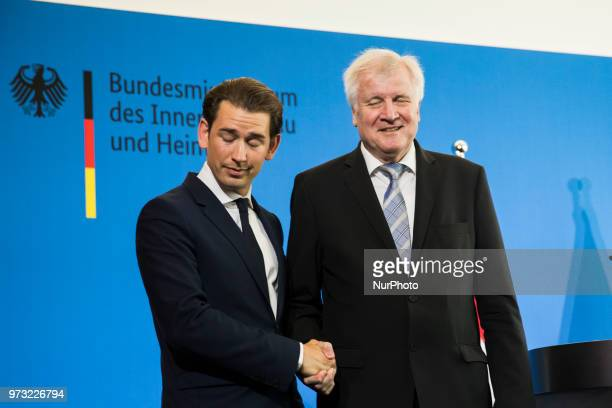 German Interior Minister Horst Seehofer and Austrian Chancellor Sebastian Kurz shake hands at the end of a press conference at the Interior Ministry...