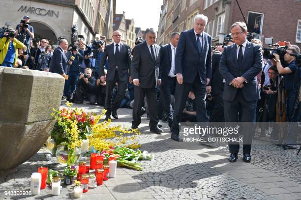 TOPSHOT German Interior Minister Horst Seehofer and State leader in North RhineWestphalia Armin Laschet pay their respect at a makeshift memorial at...