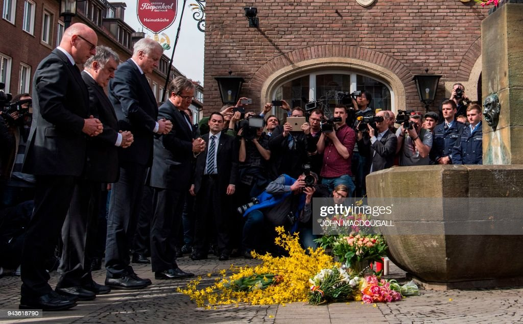 TOPSHOT - German Interior Minister Horst Seehofer (3rdL) and State leader in North Rhine-Westphalia Armin Laschet (4th L) pay their respect at a makeshift memorial at the square where a man ploughed with a van into an open-air restaurant, killing two people a day earlier in Muenster, western Germany on April 8, 2018. / AFP PHOTO / John MACDOUGALL
