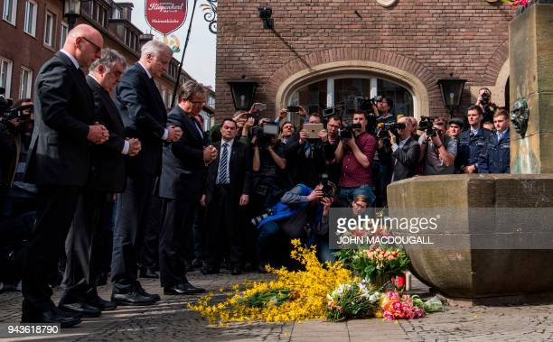 German Interior Minister Horst Seehofer and State leader in North Rhine-Westphalia Armin Laschet pay their respect at a makeshift memorial at the...