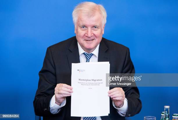 """German Interior Minister Horst Seehofer holds a copy of his """"master plan"""" concerning migration policy on July 10, 2018 in Berlin, Germany. The plan..."""