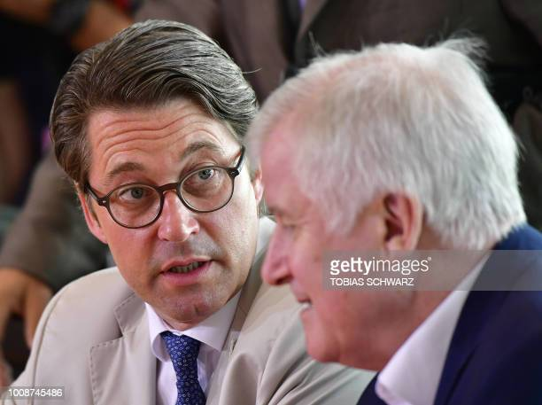 German Interior Minister Horst Seehofer talks with German Transport Minister Andreas Scheuer before the start of the weekly cabinet meeting in Berlin...