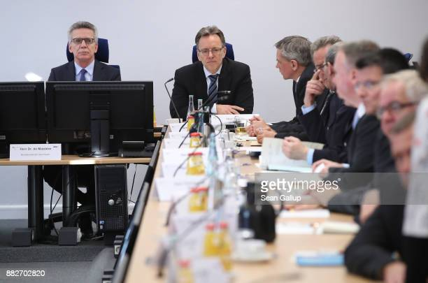 German Interior Minister Thomas de Maiziere and Federal Criminal Office President Holger Muench speak to colleagues about the current state of...