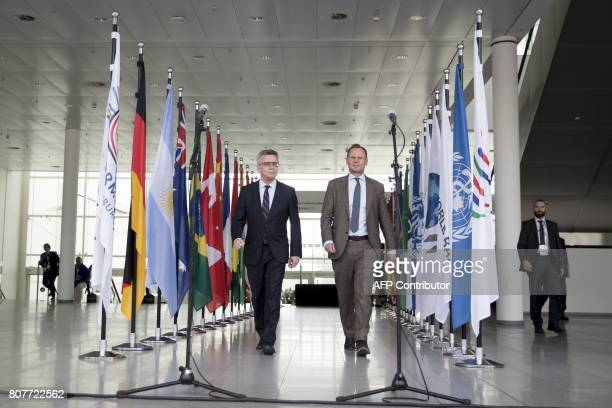 German Interior Minister Thomas de Maiziere and Hamburg's Interior Senator Andy Grote arrive to give a statement next to the flags of the G20...