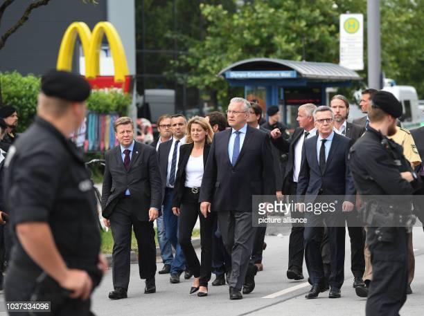 German Interior Minister Thomas de Maiziere Bavaria's Interior Minister Joachim Herrmann arrive at the Olympia Einkaufszentrum one day after a...