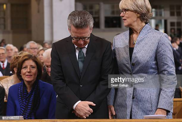 German Interior Minister Thomas de Maiziere bows his head as his wife Martina and Governor of RhinelandPalatinate Malu Dreyer arrive for a...