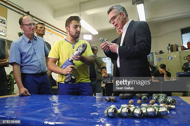 German Interior Minister Thomas de Maiziere chats with a trainee in a systems mechanics class at the BWK job training center on July 21 2016 in...