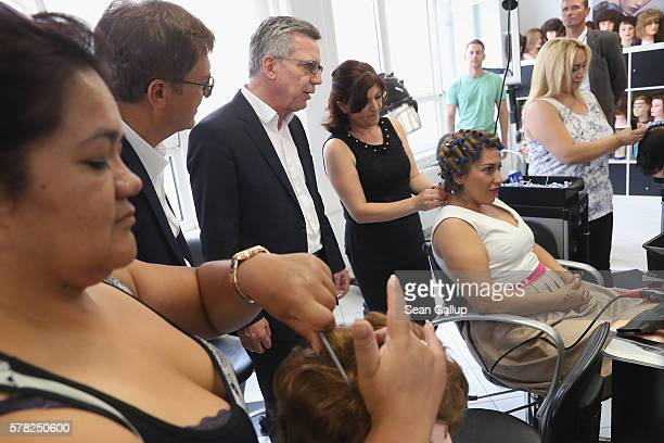 German Interior Minister Thomas de Maiziere chats with trainees in the hair salon at the BWK job training center on July 21 2016 in Berlin Germany...