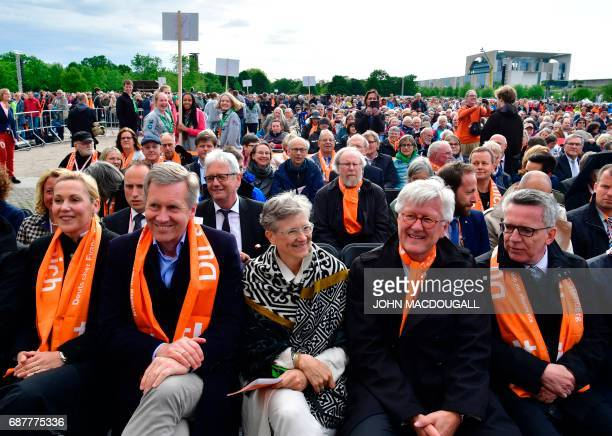 German Interior Minister Thomas de Maiziere former German President Christian Wulff and his wife Bettina Wulff attend in Berlin on May 24 2017 the...
