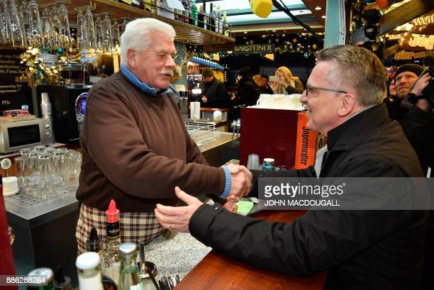 German Interior Minister Thomas de Maiziere greets a bar owner as he visits the Christmas market at Berlin's Breitscheidplatz square on December 5...