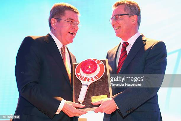 German Interior Minister Thomas de Maiziere hands over a birthday present to IOC President Thomas Bach during his 60th Birthday party at Stadthalle...