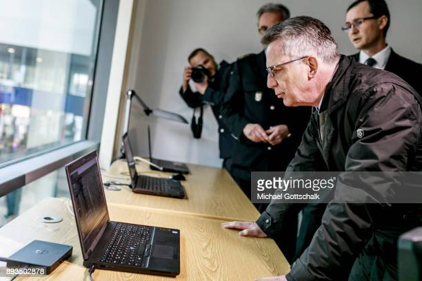 German Interior Minister Thomas de Maiziere inspects three computers with different monitoring systems during his visit to a project for automatic...