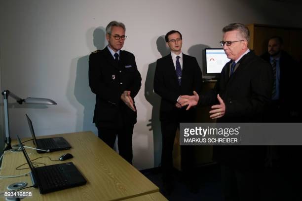 German Interior Minister Thomas de Maiziere looks at a computer running an automatic facial recognition system during a visit at the Suedkreuz train...