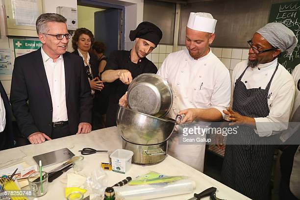 German Interior Minister Thomas de Maiziere looks on as cooking class teacher Kevin Moore instructs trainees in preparing baked Alaska in the cooking...