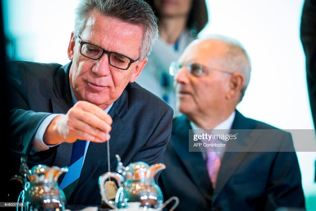 German Interior minister Thomas de Maiziere makes himself a cup of tea prior to the weekly cabinet meeting at the Chancellery in Berlin on September 13, 2017. / AFP PHOTO / Odd ANDERSEN