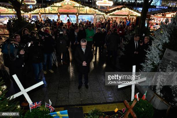 German Interior Minister Thomas de Maiziere pays his respects at a makeshift memorial for the victims of Berlin's Christmas market attack at...