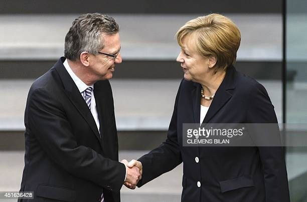German Interior Minister Thomas de Maiziere shakes hands with German chancellor Angela Merkel during a plenary session at the Lower House of...