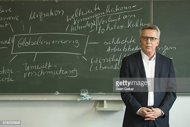German Interior Minister Thomas de Maiziere stands next to a chalk board with concepts related to globalization on it in an advanced German language...