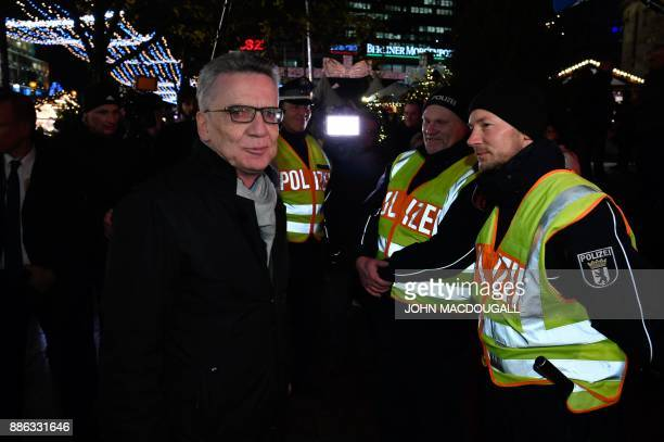 German Interior Minister Thomas de Maiziere talks with policemen taking care of the security of the Christmas market at Breitscheidplatz square in...