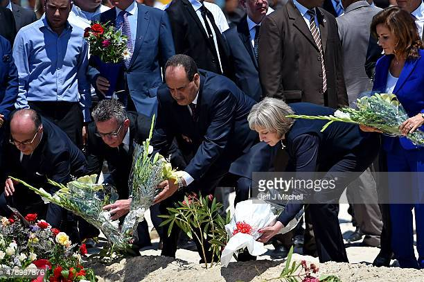 German Interior Minister Thomas de Maiziere Tunisia's Interior Minister Mohamed Gharsalli and British Home Secretary Theresa May lay flowers at the...