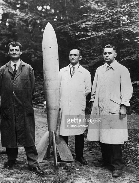 German inventor Professor Oberth left seen with two colleagues and their first successful rocket at the Jungerheide research station It is claimed to...