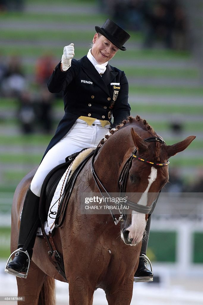 German Isabell Werth rides Bella Rosa 2 on August 26, 2014 during the second session of the Dressage Grand Prix of the 2014 FEI World Equestrian Games at D'Ornano Stadium in the northwestern French city of Caen. TRIBALLEAU
