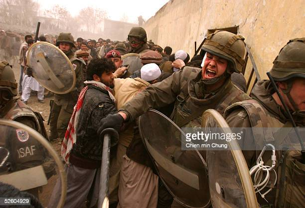 German ISAF peacekeeper controls a crowd at a soccer game on February 15, 2002 in Kabul, Afghanistan. Only a limited number of tickets were given...
