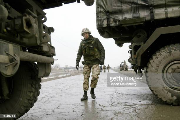 German ISAF soldier walks through two trucks blocking the site 300 meters from where an Afghan suicide bomber exploded a taxi packed with explosives...