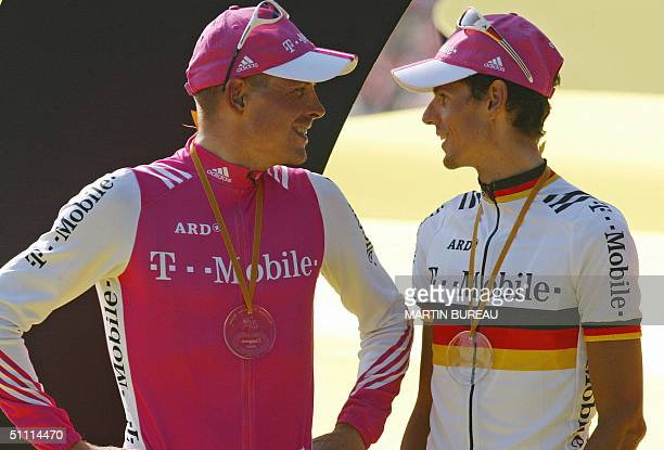 German Jan Ullrich talks to his teammate Andreas Kloden on the podium at the end of the 91st Tour de France cycling race on the Champs-Elysees in...
