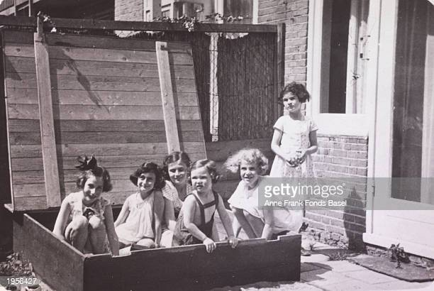German Jewish refugee Anne Frank plays in a sandbox with friends L to R Hannelie Goslar Anne Frank Dolly Citroen Hanna Toby Barbara Ledermann Sanne...