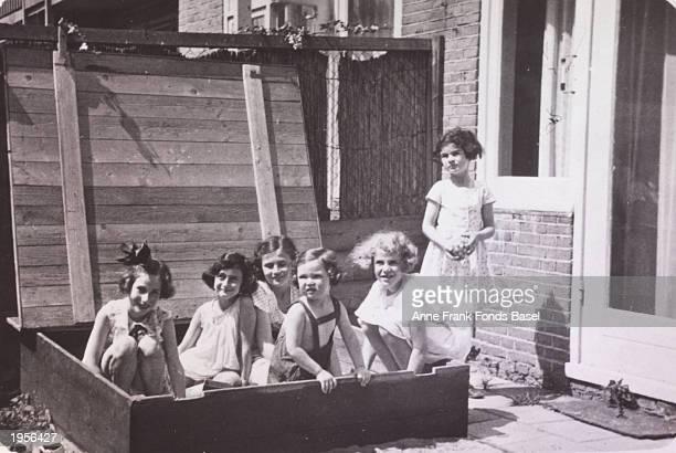 German Jewish refugee Anne Frank plays in a sandbox with friends L to R Hannelie Goslar Anne Frank Dolly Citroen Hanna Toby Barbara Ledermann Sanne...