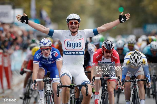 German John Degenkolb raises his arms in victory as he crosses the finish line of the 107th edition of the ParisTours cycling race on October 13 2013...