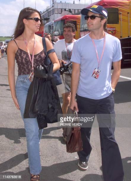 German JordanMugenHonda driver Heinz Harald Frentzen and his girlfriend Tanja walk in the paddocks of the Hungaroring racetrack in Budapest 12 August...