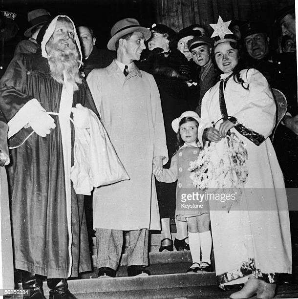 German journalist and Nazi Minister of Propaganda Joseph Goebbels holds hands with his daughter Helga as they stand on steps next to costumed...