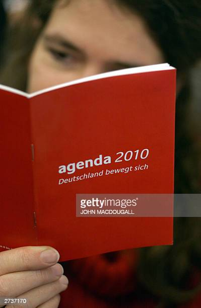 German journalist takes a look at the Social Democratic Party's little red book entitled 'Agenda 2010 Germany on the move' in a Berlin office 17...