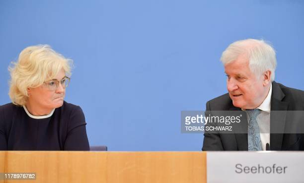 German Justice Minister Christine Lambrecht and German Interior Minister Horst Seehofer react during a presentation of the government's new measures...