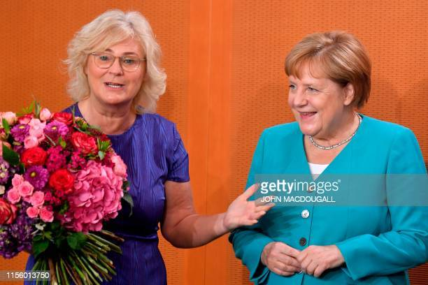 German Justice Minister Christine Lambrecht speaks before offering flowers to Chancellor Angela Merkel for her birthday during the weekly cabinet...