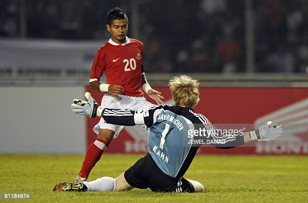 German league and Cup champions Bayern Munich goalkeeper and captain Oliver Kahn foils an attempt by Bambang Pamungkas of Indonesia during a friendly...