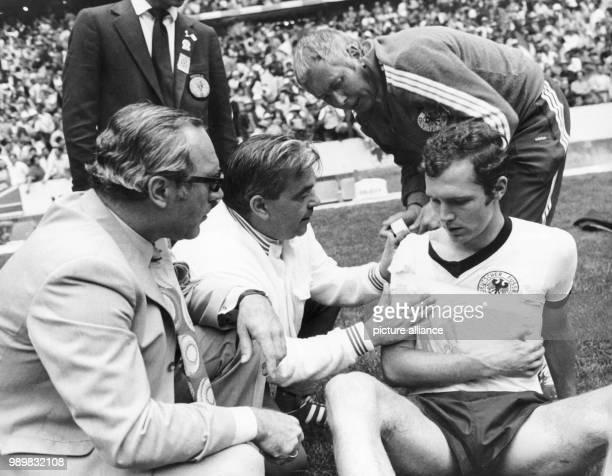 German libero Franz Beckenbauer is treated for a shoulder injury by German team doctor professor Schobert and masseur Erich Deuser during the 1970...