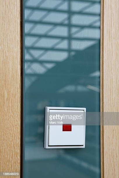 German light switch against glass reflecting a staircase