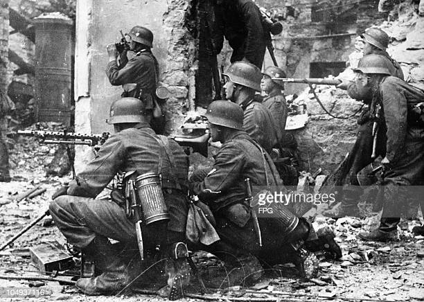 A German machine gun crew against a background of ruined houses holding their fire temporarily during streetfighting in a Soviet city during World...