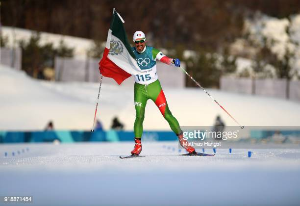 German Madrazo of Mexico holds the flag of Mexico as he approaches the finish line during the CrossCountry Skiing Men's 15km Free at Alpensia...