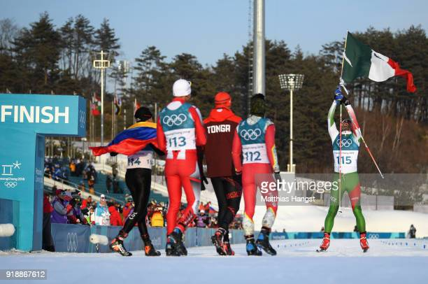 German Madrazo of Mexico holds the flag of Mexico as he crosses the finish line as Sebastian Uprimny of Colombia Samir Azzimani of Morocco Pita...