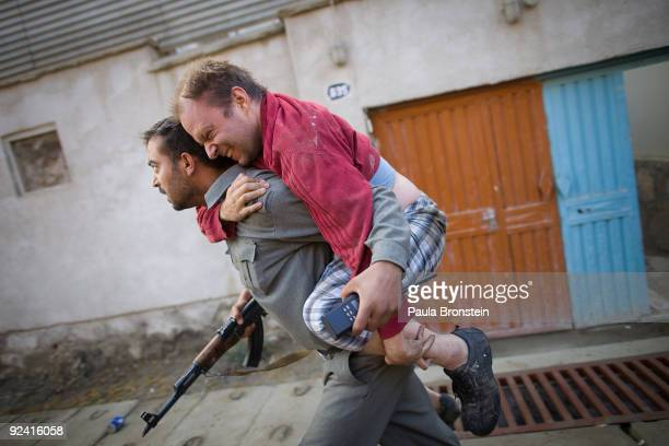 German man with a broken foot is carried away from the scene of a suicide bomb attack on an international guest house October 28, 2009 in Kabul,...