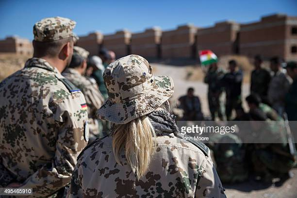 German medics watch as Kurdish Peshmerga forces learn battlefield first aid techniques during a medical training session on November 3 2015 in Erbil...
