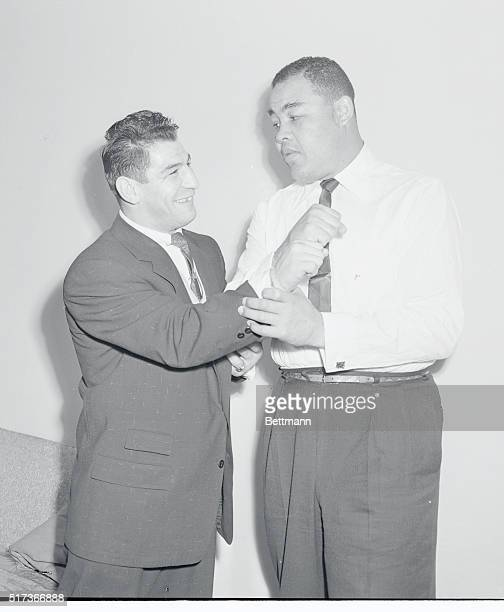 German middleweight boxer Peter Mueller matches fists with exheavyweight champ Joe Louis in Chicago after it was reported Louis had signed to train...