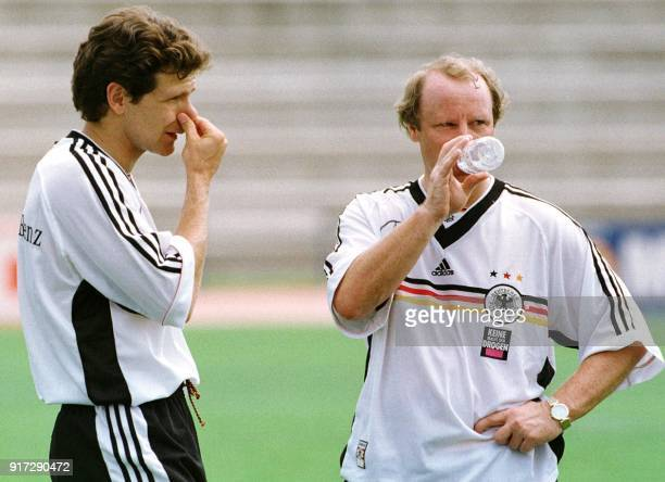 German midfielder Andreas Moeller touches his nose while coach Berti Vogts drinks some water during a training session of the German squad in Nice...