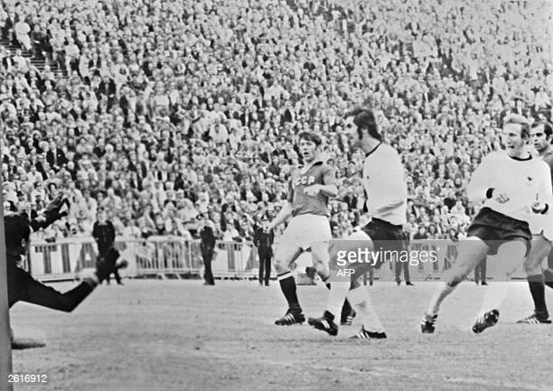 German midfielder Martin Wimmer scores against the Soviet Union as forward Gerd Muller looks on during the European Nations soccer championship final...